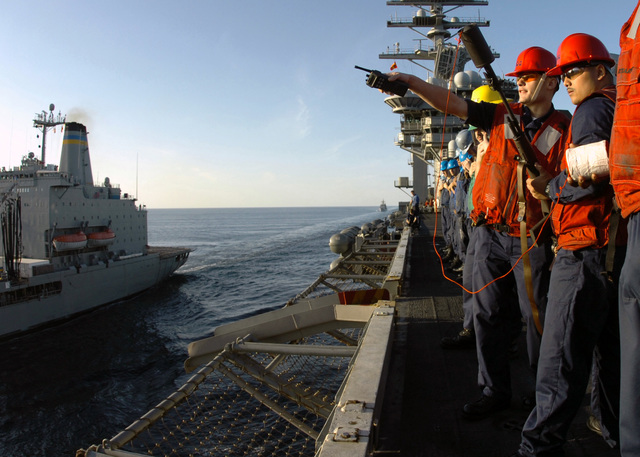 U.S. Navy Sailors, onboard the Nimitz Class Aircraft Carrier USS DWIGHT D. EISENHOWER (CVN 69), discuss where to fire their 7.62 mm. M-14 rifle with a Mark 87 line throwing attachment during an underway replenishment operation with the Military Sealift Command Henry J. Kaiser Class Oiler USNS LARAMIE (T-AO 204), (left), in the Arabian Sea on Nov. 27, 2006. (U.S. Navy photo by Mass Communication SPECIALIST SEAMAN David Danals) (Released)