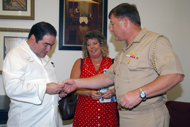 "U.S. Navy CAPT. Mathew E. Shellhorn, Commander, Navy Region Southeast CHIEF of STAFF, presents renowned culinary-genius and national television personality Emeril Lagassi, with a command coin.  The chef is visiting U.S. Navy Sailors at Naval Air Station (NAS) Jacksonville, Fla. and signing his newest book,""Emeril's There's a Chef in my World.""(U.S. Navy PHOTO by Mass Communication SPECIALIST 2nd Class Susan Cornell) (Released)"
