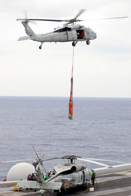 A U.S. Navy MH-60S Nighthawk helicopter from Helicopter Sea Combat Squadron 25, hovers above an SH-60B Seahawk from Helicopter Anti-Submarine Squadron Light 51, during a weapons off-load between the Aircraft Carrier USS KITTY HAWK (CV 63) and the Military Sealift Command Kilauea Class Ammunition Ship USNS FLINT (T-AE 26) in the Philippine Sea, Dec. 3, 2006. (U.S. Navy photo by Mass Communication SPECIALIST SEAMAN Thomas J. Holt) (Released)