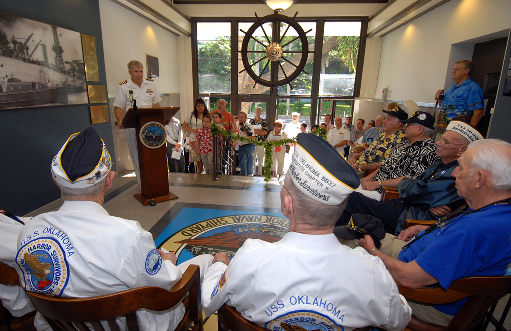 U.S. Navy CAPT. Frank J. Camelio, Commander of Pearl Harbor Naval Shipyard and Intermediate Maintenance Facility, delivers his remarks to USS OKLAHOMA survivors, seated, Ray Turpin, Jerry Tessaro, Paul Goodyear, George Smith, Raymond Richmond and James Bounds, during the Pearl Harbor Naval Shipyard's USS OKLAHOMA Lobby Display Dedication ceremony on Dec. 6, 2006, at Pearl Harbor, Hawaii.  The renovation and dedication honors the historic tie between the Pearl Harbor Shipyard workers who aided in the rescue of 32 Sailors from the capsized ship in the days following Dec. 7, 1941.  (U.S. Navy PHOTO by Mass Communication SPECIALIST 1ST Class James E. Foehl) (Released)