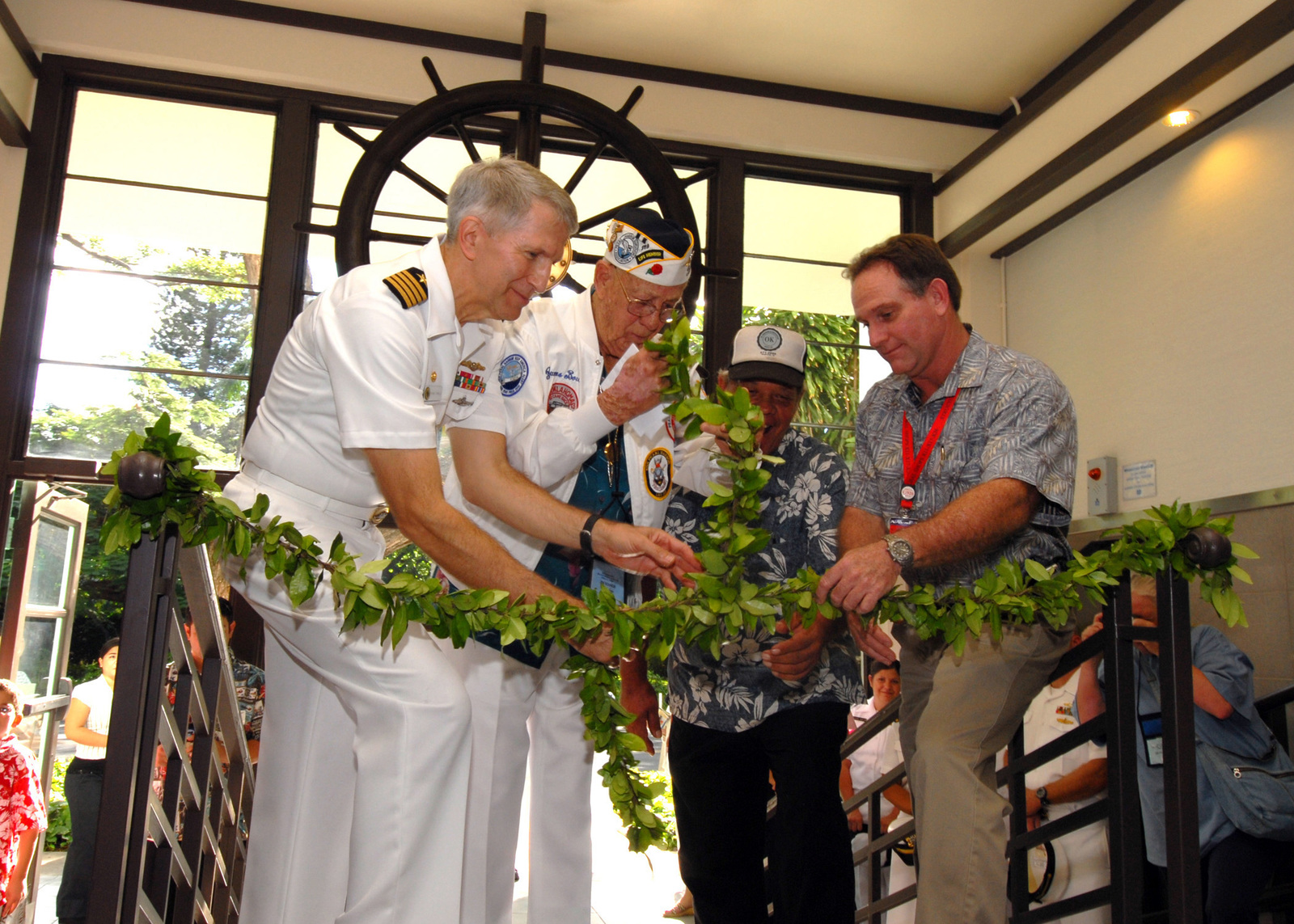 U.S. Navy CAPT. Frank J. Camelio, Commander of Pearl Harbor Naval Shipyard and Intermediate Maintenance Facility, USS OKLAHOMA survivor James Bounds, Thomas Ackerman, naval facilities foreman and Bill Sullivan, Structural Superintendent for Pearl Harbor Naval Shipyard perform the traditional Hawaiian untying of the lei, on Dec. 6, 2006, during the Pearl Harbor Naval Shipyard's USS OKLAHOMA Lobby Display Dedication ceremony at Naval Station Pearl Harbor, Hawaii. The renovation and dedication honors the historic tie between the Pearl Harbor Shipyard workers who aided in the rescue of 32 Sailors from the capsized ship in the days following Dec. 7, 1941. (U.S. Navy PHOTO by Mass...