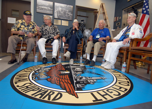 "U.S. Navy USS OKLAHOMA survivors (left to right), Ray Turpin, Jerry Tessaro, Paul Goodyear, George Smith and Raymond Richmond sit at the crest of the Pearl Harbor Naval Shipyard logo, which reads the motto,""We make them fit to fight,""during the USS OKLAHOMA Lobby Display Dedication ceremony at Naval Station Pearl Harbor, Hawaii. The motto was adopted after the events of on Dec. 7, 1941, and the shipyard's restoration of the crippled Pearl Harbor fleet. The renovation and dedication also honored the historic tie between the Pearl Harbor Shipyard workers who aided in the rescue of 32 Sailors from the capsized ship in the days following Dec. 7, 1941. (U.S. Navy PHOTO by Mass Communication..."