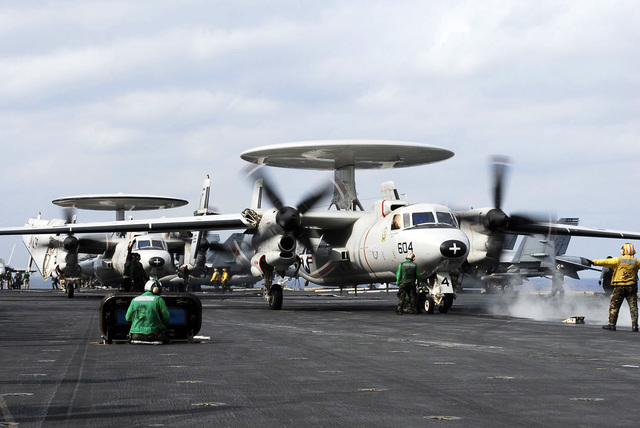 """A U.S. Navy Aircraft Director signals the pilots of an E-2C from Carrier Airborne Early Warning Squadron 115, the""""Liberty Bells,""""onto the waist catapult prior to starting flight operations aboard the Aircraft Carrier USS KITTY HAWK (CV 63) off the coast of Okinawa, Japan., Dec. 7, 2006. (U.S. Navy photo by Mass Communication SPECIALIST SEAMAN Stephen W. Rowe) (Released)"""