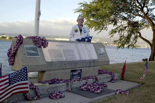A Pearl Harbor survivor poses for a picture behind the USS NEVADA Memorial at Pearl Harbor, Hawaii, on Dec. 8, 2006, during the joint Navy/National Park Service ceremonies commemorating the 65th Anniversary of the attack on Pearl Harbor.  More than 1,500 Pearl Harbor survivors, their families and their friends from around the nation joined the more than 2,000 distiguished guests and the general public for the annual Pearl Harbor observance. (U.S. Navy photo by Mass Communication SPECIALIST 1ST Class Vic Jefferies) (Released)