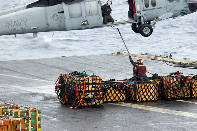 A U.S. Navy Aviation Ordnanceman hooks ammunition to a MH-60S Knight Hawk helicopter from Helicopter Sea Combat Support Squadron 25, during a vertical replenishment between the Aircraft Carrier USS KITTY HAWK (CV 63) and the Military Sealift Command Kilauea Ammunition Ship USNS FLINT (T-AE32) in the Philippine Sea, Dec. 8, 2006. (Navy photo by Mass Communication SPECIALIST SEAMAN Kyle D. Gahlau) (Released)
