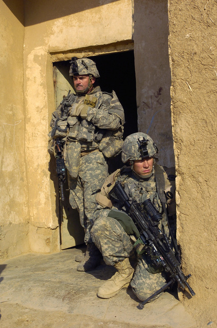U.S. Army SGT. Daniel Jarvis (standing) and SPEC. Nathan Wright, both from Alpha Company, 2nd Battalion, 27th Infantry Regiment, 2nd Infantry Division, maintain security behind cover with M4 Carbine assault rifles on Dec. 11, 2006, in the Village of Sijn, Kirkuk, Salah ad Din Province, Iraq, while searching for insurgents in support of Operation Iraqi Freedom.  (U.S. Army photo by SGT. 1ST Class Michael T. Guillort) (Released)