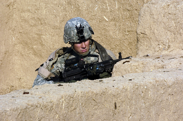 U.S. Army SPEC. Nathan Wright, Alpha Company, 2nd Battalion, 27th Infantry Regiment, 2nd Infantry Division, maintains security behind cover with an M4 Carbine assault rifle on Dec. 11, 2006, in the Village of Sijn, Kirkuk, Salah ad Din Province, Iraq, while searching for insurgents in support of Operation Iraqi Freedom.  (U.S. Army photo by SGT. 1ST Class Michael T. Guillort) (Released)