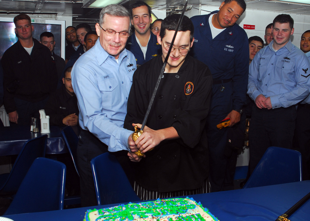The oldest and youngest crewmembers of U.S. Navy Avenger Class Mine Countermeasures Ship USS GUARDIAN (MCM 5) cut a birthday cake honoring the ship's 17th birthday on Dec. 13, 2006. The Sasebo, Japan-based GUARDIAN is serving under Task Force (CTF) 76. (U.S. Navy photo by Mass Communication Second Class Adam R. Cole) (Released)