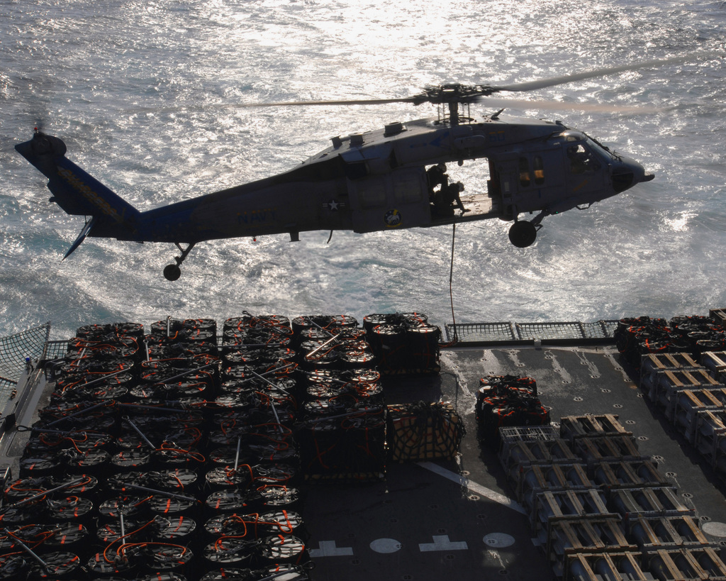 A U.S. Navy MH-60S Knighthawk helicopter assigned to Helicopter Sea Combat Squadron 26, prepares to deliver ammunition to the flight deck of the Nimitz Class Aircraft Carrier USS THEODORE ROOSEVELT (CVN 71). The THEODORE ROOSEVELT (CVN 71) is conducting a Vertical Replenishment with the Military Sealift Command Advanced Auxiliary Dry Cargo/ Ship USNS LEWIS AND CLARK (T-AKE 1) in the Atlantic Ocean, Dec. 15, 2006. (U.S. Navy photo by Mass Communication SPECIALIST SEAMAN Zach Hernandez) (Released)