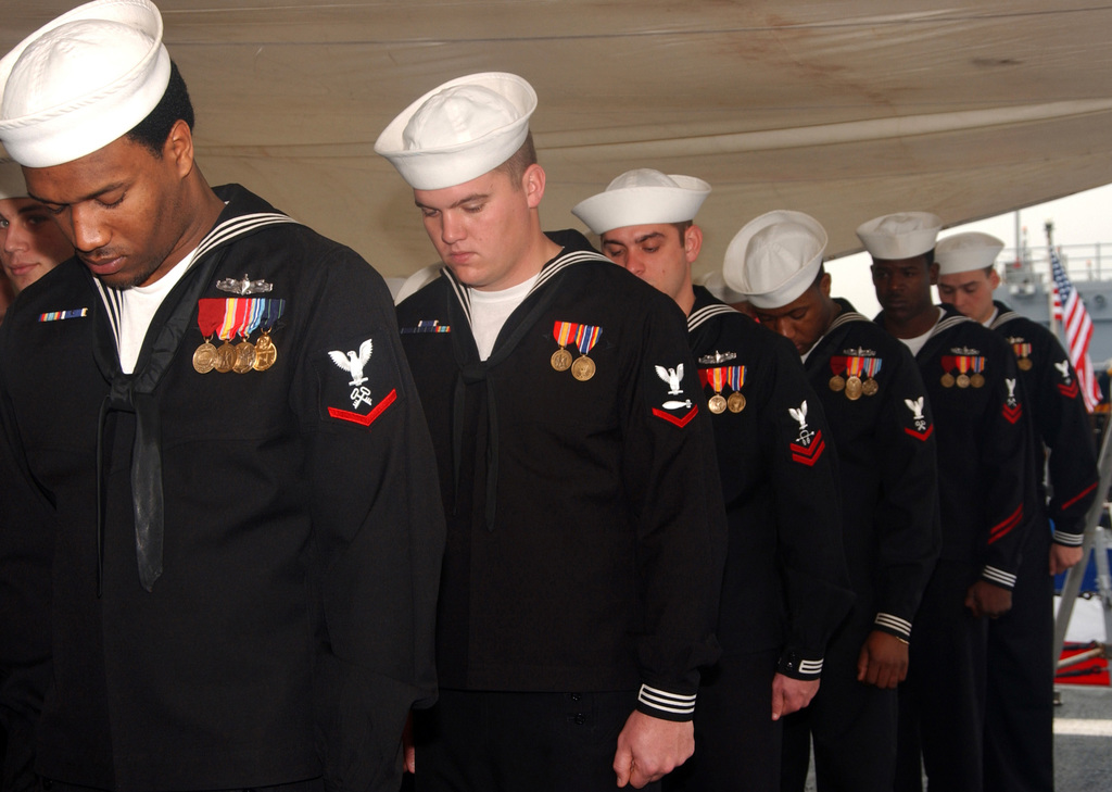 Crewmembers of the U.S. Navy (USN) Oliver Hazard Perry Class Guided Missile Frigate USS HALYBURTON (FFG 40) bow their heads in prayer during a change of command ceremony held aboard the ship. USN CMDR. William Byrne turned over command of the ship to USN CMDR. Everett Pratt on Dec. 15, 2006, at Mayport, Fla. (U.S. Navy photo by Mass Communication SPECIALIST Second Class Regina L. Brown) (Released)
