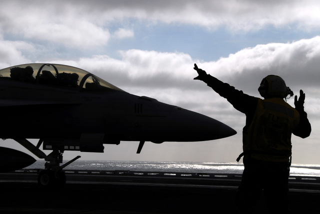 """U.S. Navy Aviations Boatswain's Mate 2nd Class Kevin Sanchez, directs an F/A-18E Super Hornet assigned to the""""Tophatters""""of Strike Fighter Squadron 41, aboard the Aircraft Carrier USS NIMITZ (CVN 68) off the coast of Southern Calif., Dec. 15, 2006. (U.S. Navy photo by Mass Communication SPECIALIST 3rd Class Roland Franklin0 (Released)"""