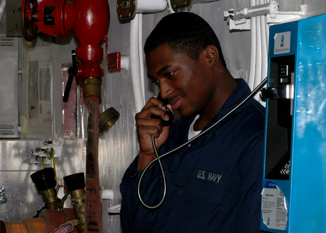 Onboard the U.S. Navy Nimitz Class Aircraft Carrier, USS DWIGHT D. EISENHOWER (CVN 69), Aviation Ordnanceman AIRMAN Apprentice Kyrie'JonFrancis talks on a pay phone with family members back home on December 18, 2006. The Eisenhower and embarked Carrier Air Wing 7 are underway in the Persian Gulf on a regularly scheduled deployment in support of Maritime Security Operations and Operation Iraqi Freedom. (U.S. Navy PHOTO by Mass Communication SPECIALIST SEAMAN Apprentice Shanika L. Futrell) (Released)
