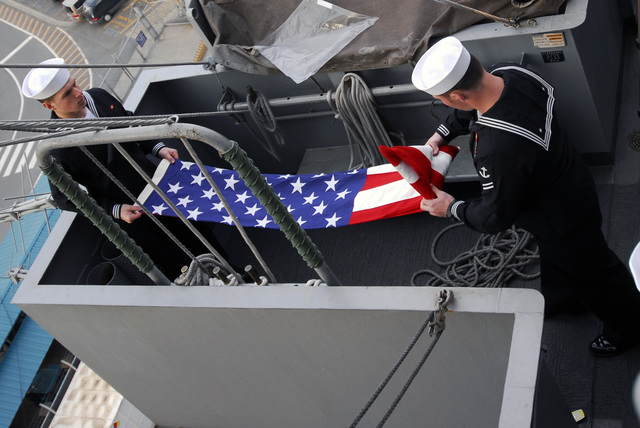 U.S. Navy Quartermaster SEAMAN Daniel Sullivan (left) and Quartermaster SEAMAN Shawn Canfield (right) properly fold the American Flag (National Standard) after flying it from the mast aboard the Kitty Hawk Class Aircraft Carrier USS KITTY HAWK (CV 63) on Dec. 20, 2006, to honor the 41st anniversary of the death of U.S Navy CAPT. Guy David Johnson. This flag covered CAPT. Johnson's casket during his funeral and was sent by his family to the KITTY HAWK to be flown for this anniversary date. CAPT. Johnson (a pilot) and LT. CMDR. Lee Edward Nordahl (a navigator) were both shot down and killed on Dec. 20, 1965, while flying a naissance mission over North Vietnam in an RA-5C Vigilante...