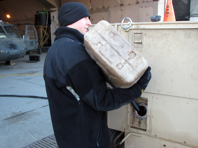 U.S. Army SPC. Jacob White, Kentucky Army National Guard assigned to Bravo Company, 449th Aviation Support Battalion, refuels an Aviation Ground Power Unit using a 5-gallon can of JP-8, at Logistic Support Area, Anaconda, Balad Air Base, Iraq, on Dec. 24, 2006, during Operation Iraqi Freedom. (A3606) (U.S. Army PHOTO by SGT. 1ST Class Orbe) (Released)