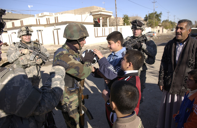 A member of an Iraqi emergency service unit gives a soccer ball to a child during a combined dismounted patrol being conducted with U.S. Army Soldiers in the district of Maghdad, Kirkuk province, Iraq, Jan. 1, 2007. The Soldiers are from Charlie Company,  2nd Battalion, 35th Infantry Regiment, 3rd Infantry Brigade, 25th Infantry Division. (U.S. Air Force photo by STAFF SGT. Samuel Bendet) (Released)