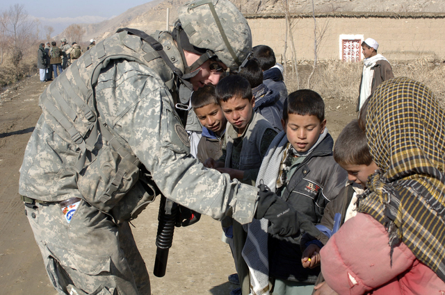 U.S. Army SPC. Kevin Santolini, of Bravo Company, 1ST Battalion, 102nd Infantry Regiment, interacts with children in Dingak, Afghanistan, Jan. 3, 2007. Soldiers with Santolini's unit are working with locals in the village to gain information on possible enemy activity. (U.S. Army photo by STAFF SGT. Michael L. Casteel) (Released)