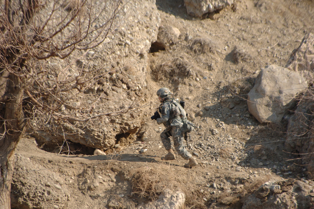 U.S. Army STAFF SGT. Michael Casteel, with 982nd Combat Camera Company (Airborne), walks up the side of a hill to look at caves near the village of Showki in the Kabisa province of Afghanistan Jan. 3, 2007. (U.S. Army photo by SGT. Isaac A. Graham) (Rele ased)