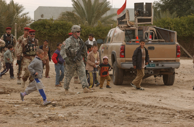 U.S. Army CAPT. Rufus Schumate, the commander of Charlie Company, 3rd Battalion, 509th Parachute Infantry Regiment, and Iraqi army soldiers are greetd by Iraqi children as they arrive to deliver humanitarian aid packages in the village of Al Hak, Iraq, J an. 5, 2007. Soldiers with Schumate's unit, an element of the 4th Brigade (Airborne), 25th Infantry Division and Iraqi army soldiers are working together to ensure security and stability in the region. (U.S. Army photo by STAFF SGT. Sean A. Foley) (Released)