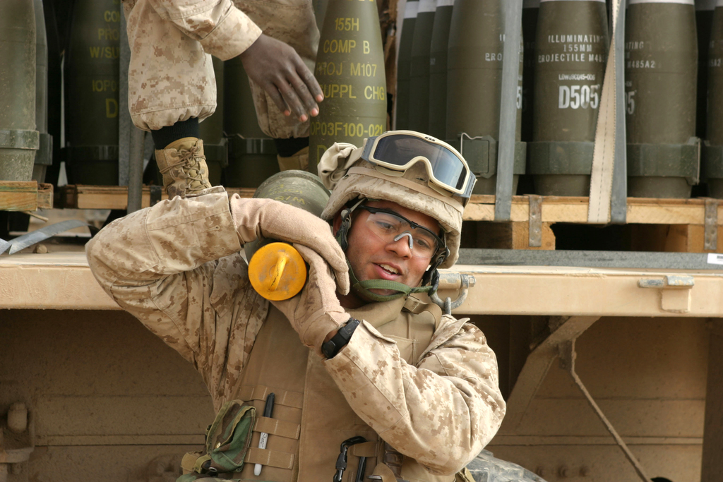 A U.S. Marine carries a round in preparation to fire a 155mm howitzer near Baghdadi, Iraq, on Jan. 6, 2007.  The Marines are with Lima Battery, 2nd Battalion, 13th Marine Regiment.  (U.S. Marine Corps photo by SGT. Jacob E. Brewer) (Released)