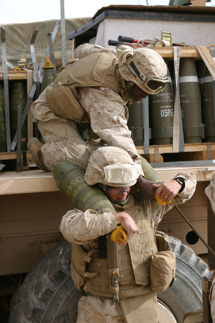 U.S. Marines with Lima Battery, 2nd Battalion, 13th Marine Regiment carry rounds in preparation to fire a howitzer near Baghdadi, Iraq, Jan. 6, 2007. (U.S. Marine Corps photo by SGT. Jacob E. Brewer) (Released)