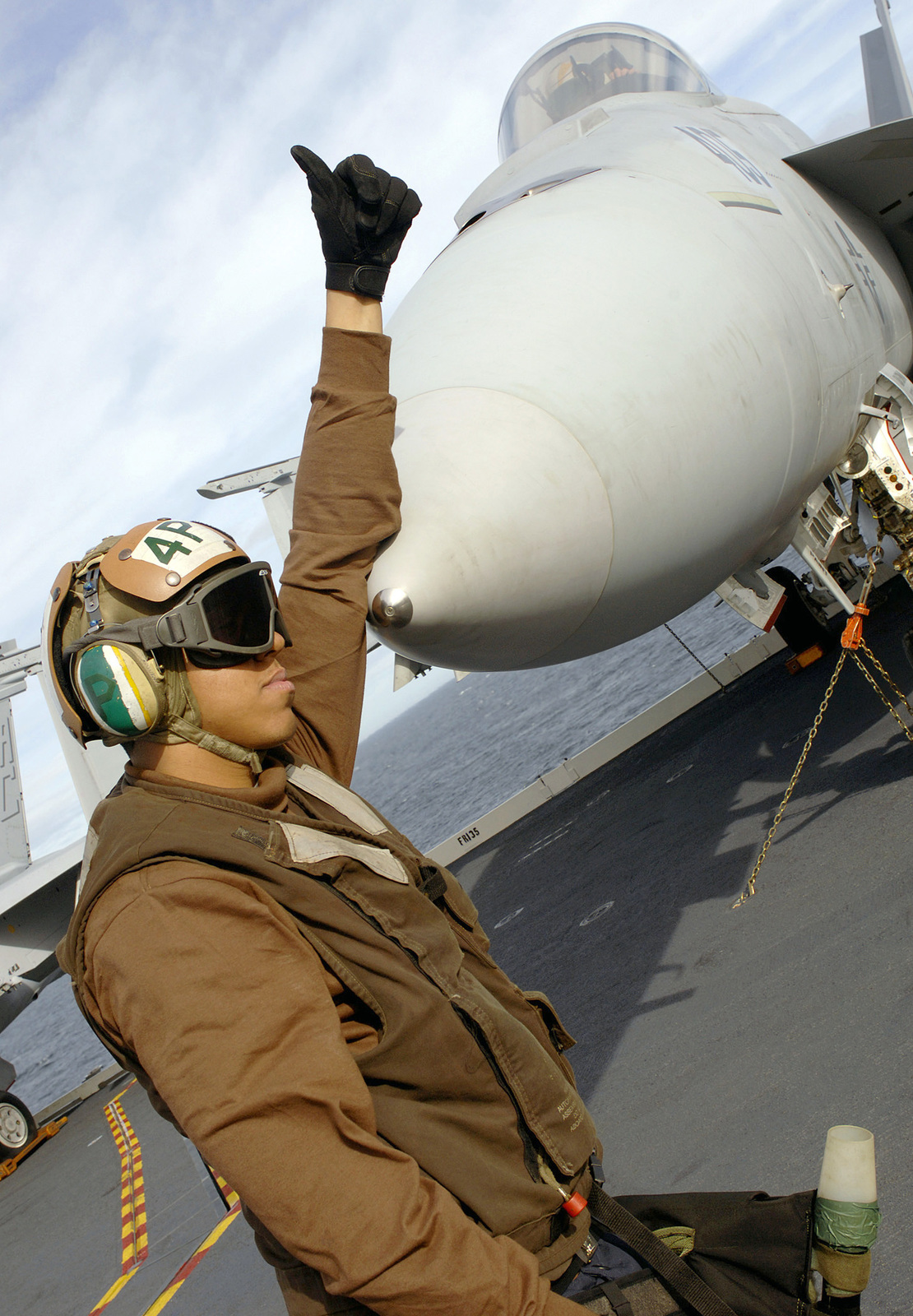"""A U.S. Navy Strike Fighter Squadron 105 (VFA-105,""""Gunslingers"""") Plane Captain gives the thumbs-up signal after completing pre-flight checks with one of his F/A-18E Super Hornet multi-mission fighter/attack aircraft pilots prior to afternoon flight operations on the flight deck of the Nimitz Class Aircraft Carrier USS HARRY S. TRUMAN (CVN 75), on Jan. 15, 2007, while the TRUMAN is currently underway conducting flight deck certifications off of the east coast in the Atlantic Ocean. (U.S. Navy photo by Mass Communication SPECIALIST 3rd Class Kristopher Wilson) (Released)"""
