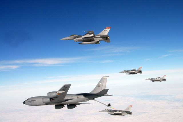 """A U.S. Air Force KC-135 Stratotanker (foreground), 319th Air Refueling Wing, refuels one of four F-16 Fighting Falcon aircraft, 119th Fighter Wing (FW), North Dakota Air National Guard (NDANG), somewhere over North Dakota on Jan. 16, 2007.  The aircraft are flying to the Aerospace Maintenance and Regeneration Center, nicknamed the""""boneyard,""""Tucson, Ariz., where they will be retired. This final flight is part of a 60th Anniversary Celebration of the NDANG and a send-off of the Falcon. The 119th FW is transitioning from the F-16 to the C-21 Learjet to support a new mission. (U.S. Air Force photo by SENIOR MASTER SGT. David H. Lipp) (Released)"""