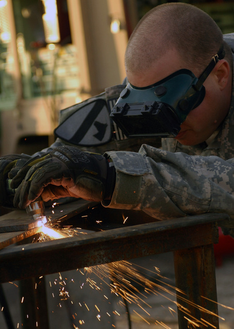 U.S. Army SPC. Gary Parks, assigned to Echo Company, 27th Base Support Battalion, 1ST Cavalry Division, cuts a notch into a metal bracket, while working at the motor pool. The Fort Bliss, Texas, fabricator helped engineer a metal bracket to secure the rocket-propelled grenade deflection cage usually attached to the M113 Armored Personnel Carrier and redesigned it to mount on an engineer route clearance vehicle for added force protection for forces in the Mosul. (U.S. Army PHOTO by STAFF SGT. Samantha M. Stryker) (Released)