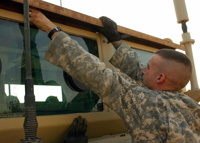 U.S. Army SPC. Kyle Thomas, a track vehicle mechanic assigned to Echo Company, 27th Base Support Battalion, 1ST Cavalry Division, braces a mounting bracket onto an engineer vehicle at the motor pool.  The Fort Bliss, Texas, vehicle mechanic helped engineer a metal bracket to secure the rocket-propelled grenade deflection cage usually attached to the M113 Armored Personnel Carrier and redesigned it to mount on an engineer route clearance vehicle for added force protection for forces in the Mosul. (U.S. Army PHOTO by STAFF SGT. Samantha M. Stryker) (Released)