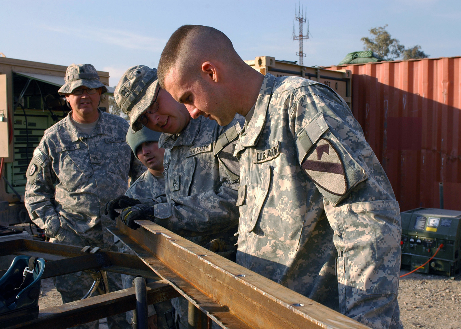 U.S. Army SPC. Kyle Thomas, SPC. Gary Parks, PFC. Paxton White and STAFF SGT. David W Finney, (front to back) are assigned to Echo Company, 27th Base Support Battalion, 1ST Cavalry Division, scrutinize a metal bracket at the motor pool. The Fort Bliss, Texas, fabricators engineered the metal bracket to secure the rocket-propelled grenade deflection cage usually attached to the M113 Armored Personnel Carrier and redesigned it to mount on an engineer route clearance vehicle for added force protection for forces in the Mosul. (U.S. Army PHOTO by STAFF SGT. Samantha M. Stryker) (Released)