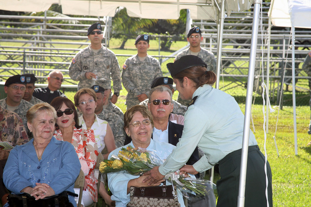 U.S. Army SGT. 1ST Class Valles (right), 166th Regional Support Group (RSG), presents flowers to Ida Miranda, the mother of COL. Fernando Fernandez, incoming Commander, 166th RSG, on the parade field on Jan. 21, 2007, at Fort Buchanan, P.R., during the 166th RSG Assumption of Command Ceremony. (U.S. Army photo by Joseph Bonet) (Released)
