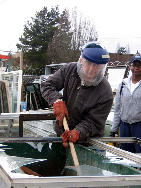 U.S. Navy Ordnanceman 2nd Class Shane Morris uses a sledgehammer to break an old window for recycling at the Habitat for Humanity Resale Store, Bremerton, Wa., on Jan. 25, 2007.  (U.S. Navy photo by Mass Communication SPECIALIST 1ST Class Krishna Jackson) (Released)