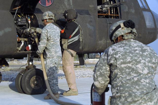 U.S. Army STAFF SGT. Jimmie Sipes (rear, right), Alpha Company, 7th Battalion, 158th Aviation Regiment, assists another Soldier from the 82nd Airborne Division to refuel a CH-47 Chinook helicopter on Jan. 26, 2007, at Camp Blessing, Afghanistan, during Operation Enduring Freedom. (U.S. Army photo by STAFF SGT. Michael Casteel) (Released)