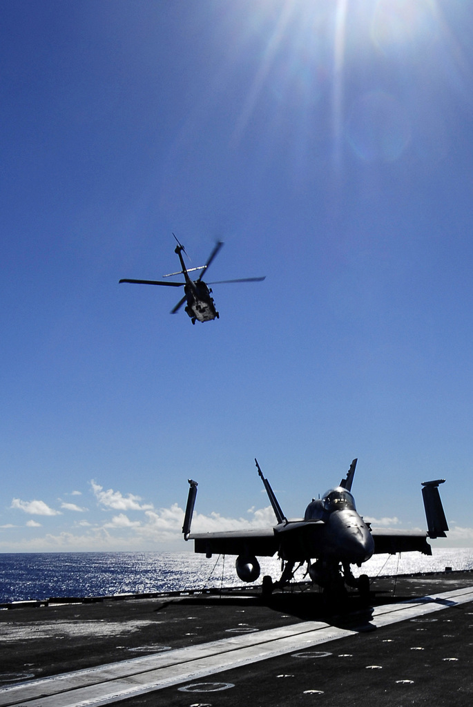 A U.S. Navy SH-60F Seahawk helicopter assigned to the Helicopter Anti-Submarine Squadron (HS) 8 takes off over the flight deck of the Nimitz Class Nuclear-Powered Aircraft Carrier USS JOHN C. STENNIS (CVN 74) on Jan. 28, 2007, during carrier qualifications somewhere in the Pacific Ocean.  An F/A-18 Hornet aircraft can be seen parked on the flight deck.  (U.S. Navy photo by Mass Communication SPECIALIST 3rd Class Jon Hyde) (Released)