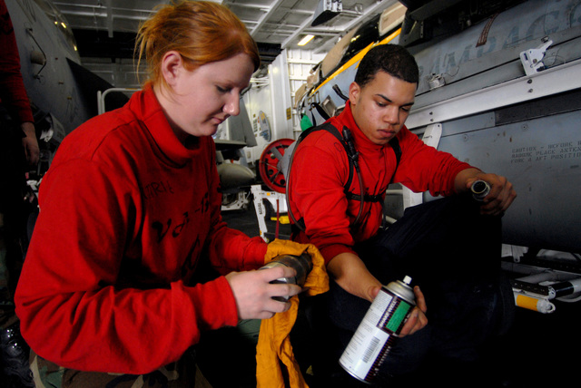 "U.S. Navy Aviation Ordnanceman AIRMAN Juan Ovales (right) hands tools to Aviation Ordnanceman 3rd Class Katherine Gutherie (left) as they perform maintenance on a bomb rack injection foot, for a a Tactical Electronic Warfare Squadron 138 (VAQ-138,""Yellowjackets"") EA-6B rowler electronic warfare aircraft, in the hangar bay aboard the Nimitz Class Aircraft Carrier USS JOHN C. STENNIS (CVN 74) on Jan. 28, 2007, while the STENNIS and Carrier Air Wing 9 (CVW-9) are conducting carrier qualifications of the coast of Southern California prior to transiting west to bolster security in the U.S. Central Command Area of Operations. (U.S. Navy photo by Mass Communication SPECIALIST 3rd Class aul J...."