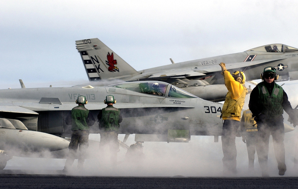 """U.S. Navy Nimitz Class Aircraft Carrier USS RONALD REAGAN (CVN 76) Flight Deck Sailors prepare a Strike Fighter Squadron 113 (VFA-113,""""Stingers"""") F/A-18E Super Hornet multi-mission fighter/attack aircraft (front) for launch as a VFA-22 (""""Fighting Redcocks"""") F/A-18E (back) performs a touch-and-go operation on Jan. 28, 2007, while the REAGAN and its strike group are currently underway on a surge deployment in support of U.S. military operations in the western Pacific Ocean. (U.S. Navy photo by Mass Communication SPECIALIST 2nd Class Aaron Burden) (Released)"""