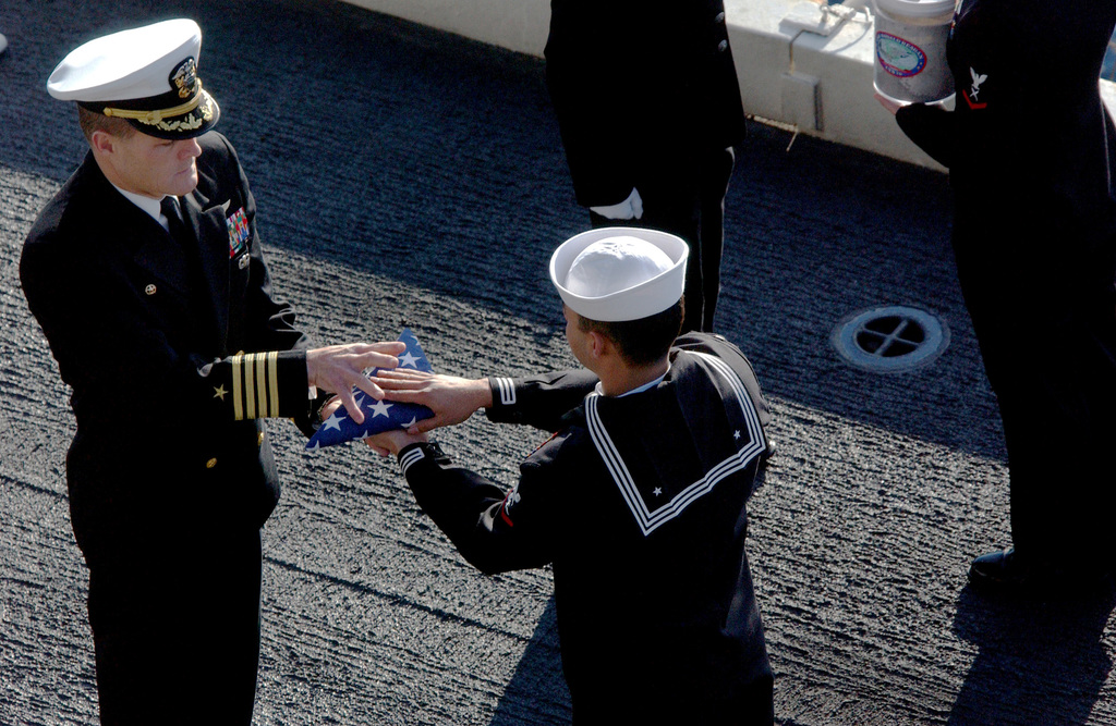 U.S. Navy Aviation Structural Mechanic 3rd Class Jose Marrero (right) presents the folded flag to CAPT. Craig Williams, Commander, Carrier Air Wing (CVW) 14, during a burial at sea ceremony aboard the Nimitz Class Nuclear-Powered Aircraft Carrier USS RONALD REAGAN (CVN 76) on Jan. 30, 2007, somewhere in the Pacific Ocean.  Two Navy Veterans are being committed to their final resting place. (U.S. Navy photo by Mass Communication SPECIALIST SEAMAN Kathleen Gorby) (RELEASED)