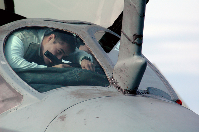 """A U.S. Navy Tactical Electronic Warfare Squadron 139 (VAQ-139,""""Cougars"""") Troubleshooter squeezes under the windshield of an EA-6B Prowler electronic warfare aircraft to inspect its aircraft control console while the aircraft is parked on the flight deck aboard the Nimitz Class Aircraft Carrier USS RONALD REAGAN (CVN 76) during a rain storm on Jan. 31, 2007. The REAGAN and its strike group are currently underway on a surge deployment in support of U.S. military operations in the western Pacific Ocean. (U.S. Navy photo by Mass Communication SPECIALIST SEAMAN Joshua Scott) (Released)"""