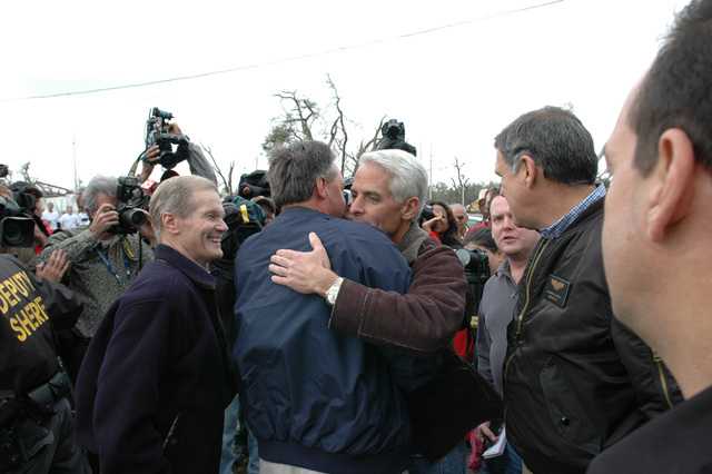 [Severe Storms and Tornadoes] Lady Lake, Fla., February 3, 2007 -- Florida Governor Charlie Crist (facing) welcomes FEMA Director David Paulison with a hug to this central Florida town as U.S. Senators Bill Nelson (D-FL) (left) and Mel Martinez (R-FL) (right) look on.  The director is there to view the damage from and described how FEMA is responding to the tornadoes that struck central Florida last night.  Mark Wolfe/FEMA