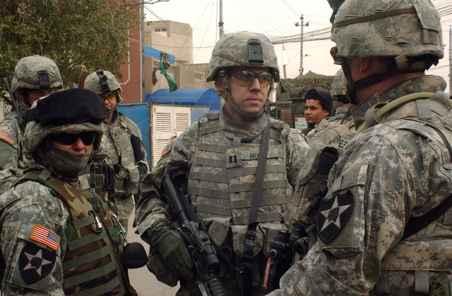 U.S. Army CAPT. Jeffrey Noll (center) and STAFF SGT. Scott Wheeler (right), both from Black Hawk Company, 1ST Battalion, 23rd Infantry Regiment, 2nd Infantry Division, discuss the current mission on Feb. 6, 2007, in Baghdad Province, Iraq, during Operation Iraqi Freedom.  (U.S. Army photo by SGT. Tierney P. Nowland) (Released)