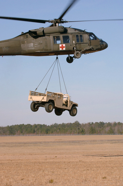 A U.S. Army UH-60Q Medical Evacuation helicopter, 54th Troop Command, sling loads a High-Mobility Multipurpose Wheeled Vehicle (HMMWV) on Feb. 16, 2007, at Blackstone Army Airfield, Va., during Operation Granite Triangle, a joint service exercise.  (U.S. Army photo by CPL. Joshua Balog) (Released)