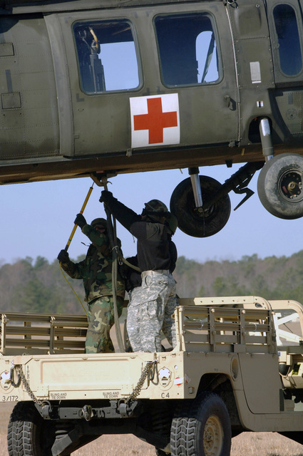 U.S. Army Soldiers, 54th Troop Command, hook up a High-Mobility Multipurpose Wheeled Vehicle (HMMWV) to a UH-60Q Medical Evacuation (MEDEVAC) helicopter for sling load transportation on Feb. 16, 2007, at Blackstone Army Airfield, Va., during Operation Granite Triangle, a joint service exercise.  (U.S. Army photo by CPL. Joshua Balog) (Released)