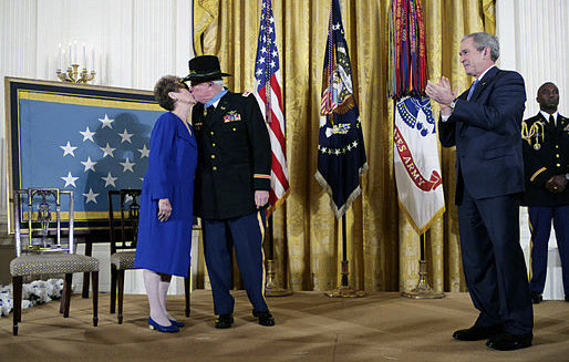 President George W. Bush (right) applauds as Medal of Honor recipient LT. COL. Bruce Crandall (U.S. Army, ret.) kisses his wife, Arlene, in the East Room of the White House on Feb. 26, 2007. LT. COL. Crandall was awarded the Medal of Honor for his heroism as a U.S. Army 1ST Cavalry Division helicopter flight commander during the Vietnam War in November 1965. (DoD photo by Eric Draper, CIV) (Released)