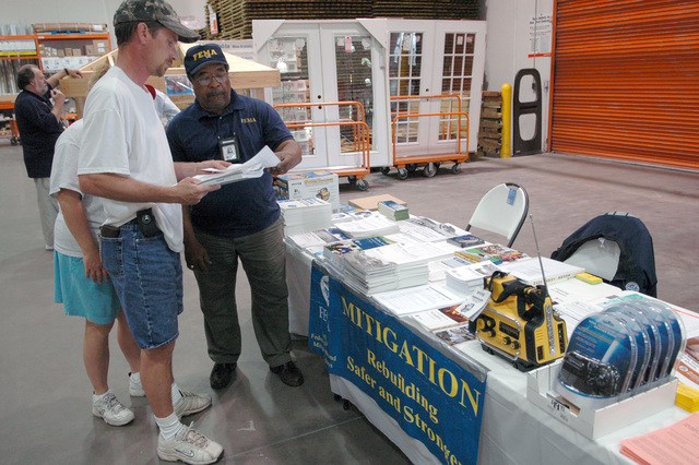 [Severe Storms and Tornadoes] Port Orange, FL, February 26, 2007 -- FEMA community relation (CR) specialist Mack Gardner (right) hands out mitigation literature to a local resident. FEMA promotes rebuilding damaged homes and building new homes in ways that resist damaging winds.  Mark Wolfe/FEMA