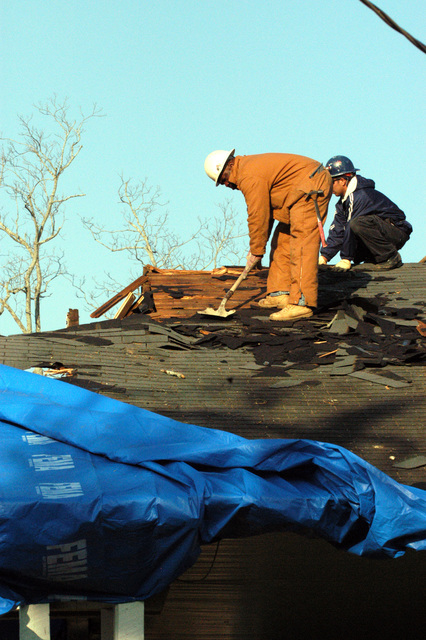 [Severe Storms and Tornadoes] Americus, GA, March 8, 2007 -- Roofers begin to repair this damaged roof that has been temporarily covered by a FEMA blue tarp.  The blue roofs are only a temporary measure to keep interiors dry until a roof can be repaired.  Mark Wolfe/FEMA