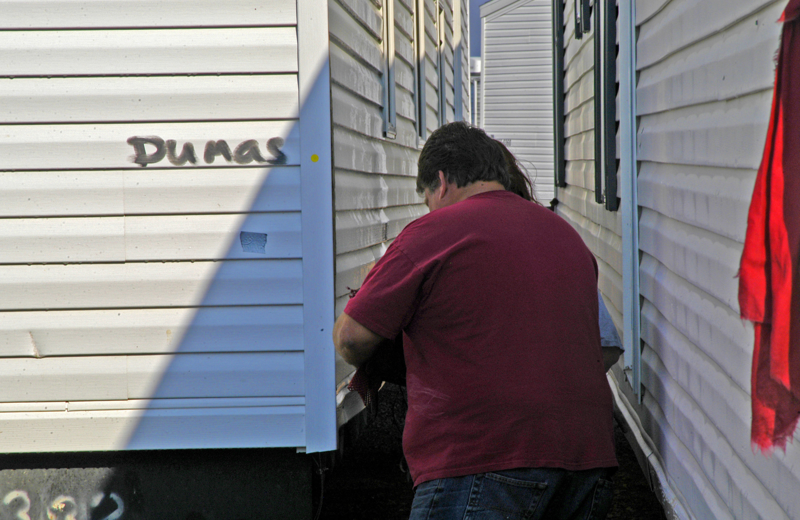 HOPE, AR, March 10, 2007 -- A mobile home technician conducts a final check on one of 23 mobile homes going to Dumas, AR to house residents recently left homeless by tornadoes.  FEMA Photo by Win Henderson