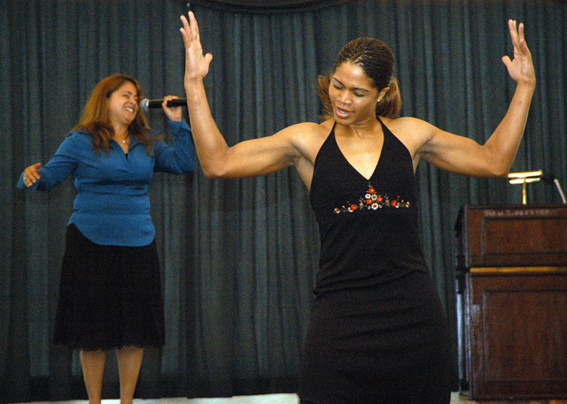 SGT. Miranda Brown, of Headquarters and Service Battalion, Marine Corps Base, performs an artistic dance along side a vocal performance by Ms. Nini Adcock during the Women's History Month Celebration hosted by Marine Corps Base Camp S. D. Butler, Okinawa, Japan at the Butler Officers Clubon March. 5, 2007. (U.S. Marine Corps photo by STAFF SGT. Ricardo Morales) (Released)