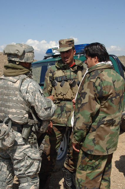 U.S. Army SGT. 1ST Class Rudolph Leonard, from the 203rd Regional Police Advisory Team, talks to an Afghan National Police officer who is needing medical attention March 22, 2007, at the Bara Border checkpoint in the Gorbuz District of Khowst Province, Afghanistan. (U.S. Army photo by STAFF SGT. Isaac A. Graham) (Released)