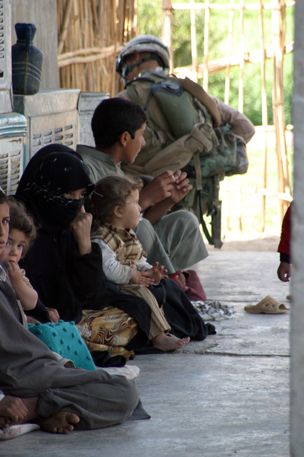 A local Iraqi family sits outsid of thir hous as Marins with 3rd Platoon, E Company, 2nd Battalion, 7th Marins sarch th surrounding ara for Anti Iraqi Forc activity during Opration Zaidon II on March 23, 2007. Task Forc 2nd Battalion, 7th Marins is conducting Opration Zaidon II in Zaidon, Iraq to clar th city of Anti Iraqi Forcs and dny thm furthr us of th ara in th futur. Rgimntal Combat Tam 6 is dployd with Multi National Forcs-Wst in support of Opration Iraqi Frdom in th Anbar Provinc of Iraq to dvlop Iraqi Scurity Forcs, facilitat th dvlopmnt of official rul of law through dmocratic rforms, and continu th dvlopmnt of a markt basd...