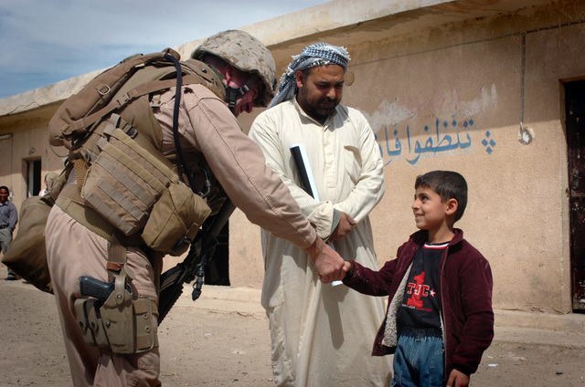 U.S. Marine Corps MAJ. Greg Hendrix attached to Lima Company, Second Battalion Tenth Marines (Lima 2/0), Second Marine Division, Second Marine Expeditionary Force shakes a students hand after speaking to the local Imam in the courtyard of a local school in Namer on March 26, 2007. Lima 2/0 provided medical supplies, hygiene item and soccer balls to the students during a one day mission to the school. Lima 2/0 is deployed with Multi National Forces-West in support of Operation Iraqi Freedom in the Ambar Province of Iraq to develop Iraqi security forces, facilitate the development of official rule of law through democratic reforms and continue the development of a market based economy...