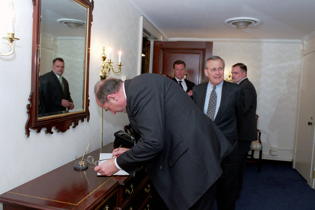 Australian Minister of Defense Peter Reith, foreground, signs guest book while U.S. Secretary of Defense, the Honorable Donald H. Rumsfeld, looks on during his visit at the Pentagon, Washington, D.C., on May 1, 2001. OSD Package No. 010501-D-2987S-001 to 008 (PHOTO by Helene C. Stikkel) (Released)